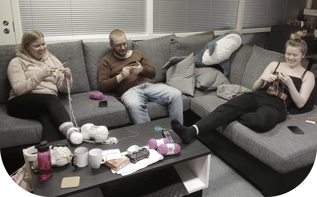 Team sitting on a sofa and knitting